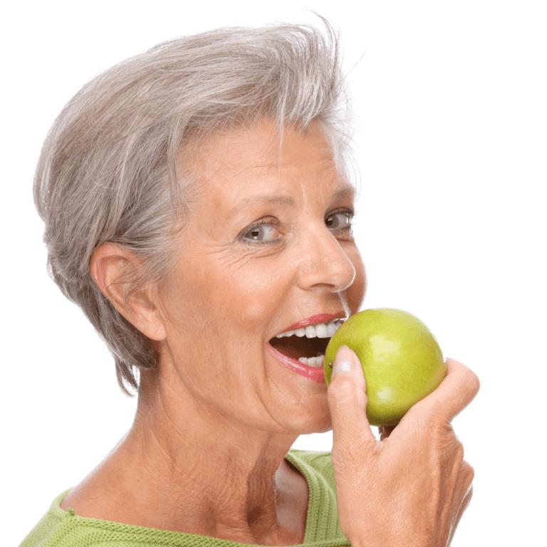 Dame med friske tenner spiser eple